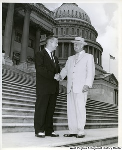 Congressman Arch A. Moore, Jr. shaking the hand of an unidentified man.