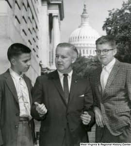 Congressman Arch A. Moore, Jr. with two unidentified young men. The Capitol Building can be seen in the background.