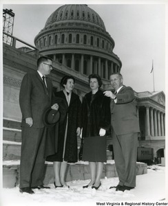 Congressman Arch A. Moore, Jr. pointing out something to three unidentified people. They are standing in the snow in front of the Capitol Building, which is under construction.