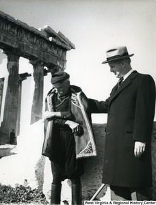 Congressman Arch A. Moore, Jr. talking to an unidentified Greek man in a coat. The edge of the Parthenon can be seen in the background.