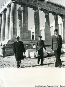 Congressman Arch A. Moore, Jr. walking away from the Parthenon in Athens, Greece. Two unidentified men are walking with him; one appears to be an officer.