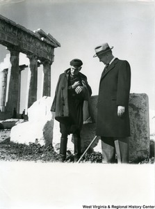 Congressman Arch A. Moore, Jr. talking to an unidentified Greek man in Athens, Greece. The edge of the Parthenon can be seen in the background.