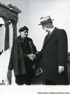 Congressman Arch A. Moore, Jr. shaking hands with an unidentified Greek man in Athens, Greece. The Parthenon can be seen in the background. A note, in Greek, is written on the back of the photograph.