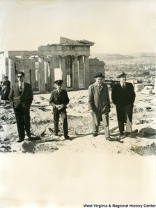 Congressman Arch A. Moore, Jr. talking with an unidentified man as they walk away from the Parthenon in Athens, Greece.  Two other unidentified men are walking with them; one appears to be a officer.