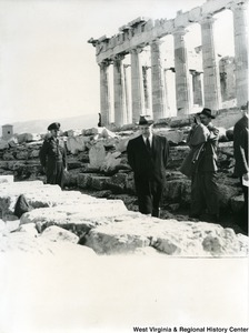 Congressman Arch A. Moore, Jr. walking around the Parthenon. An unidentified man is taking a photo behind him. An officer is also standing behind him.