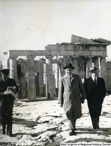 Congressman Arch A. Moore, Jr. standing outside the Parthenon with an unidentified man. An officer is also partially shown looking at some papers.