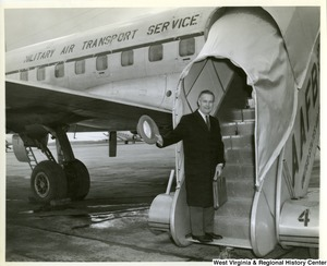 Congressman Arch A. Moore, Jr. tipping his hat in farewell from the steps of a military plane.  The side of the plane says 'Military Air Transport Services'.