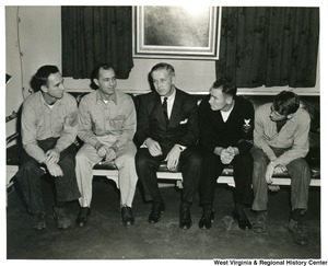 Congressman Arch A. Moore, Jr. (center) sitting on a bench with four unidentified officers on the U.S.S. Franklin D. Roosevelt.