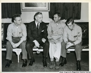 Congressman Arch A. Moore, Jr. sitting with three unidentified crew members of the U.S.S. Franklin D. Roosevelt.