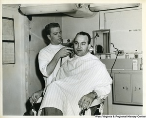 An unidentified man getting a haircut on board the U.S.S. Franklin D. Roosevelt.