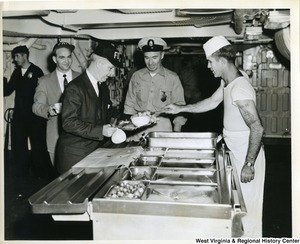 Congressman Arch A. Moore, Jr. being served food on board the U.S.S. Franklin D. Roosevelt.  Two unidentified people are also waiting to be served food.