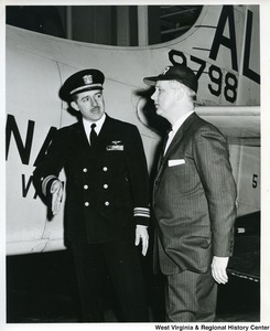 Congressman Arch A. Moore, Jr. talking with the Navy Commander of the U.S.S. Franklin D. Roosevelt. An airplane can be seen in the background.
