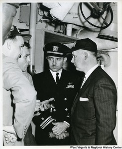 Congressman Arch A. Moore, Jr. listening to a crew member of the U.S.S. Franklin D. Roosevelt. The Commander of the Roosevelt is standing beside him.
