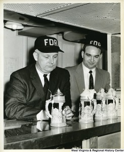 Congressman Arch A. Moore, Jr. with an unidentified man looking at some steins on the U.S.S. Franklin D. Roosevelt.