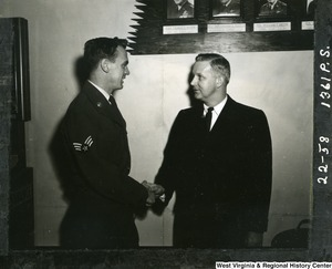 Congressman Arch A. Moore, Jr. shaking hands with Airman Marion L. Mussili after their arrival at MATS (Military Air Transport Service) Terminal, Andrews Air Force Base, Maryland from Europe. Moore interceded in the confinement of Airmen Mussili by the Greek Government after his conviction for hitting a pedestrian with a military vehicle. Moore then brought the airman back to the states with him.