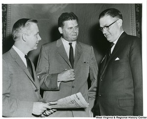 Congressman Arch A. Moore, Jr. holding a newspaper and talking to Congressman Thruston B. Morton (center) of Kentucky and an unidentified congressman.