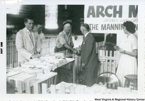 "Congressman Arch A. Moore, Jr. shaking hands with an unidentified man at the Mannington Fair. A sign at Moore's booth reads ""Arch Moore brings his office to the Mannington Fair."""