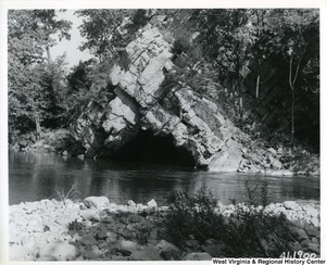 A black-and-white photograph of a fishing pool on North Fork of South Branch, Potomac River above Petersburg, W. Va. A large rock structure, shaped in an upside down V, with a cave entrance can be seen.