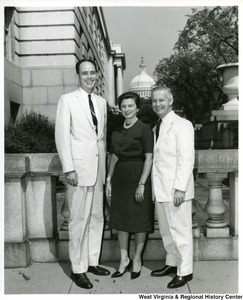 Congressman Arch A. Moore, Jr. standing with his wife, Shelley Moore, and Melvin Boyd. The Capitol Building can be seen in the background.