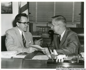 Congressman Arch A. Moore, Jr. talking to a man identified only as Buskirk.  They are sitting at Moore's desk and appear to be discussing some documents Moore is holding.