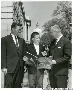 "Congressman Arch A. Moore, Jr. standing with a man identified only as Baumgardner and his son.  The son is holding a copy of ""The Capitol: A pictorial story of the Capitol in general and the House of Representatives in particular."""
