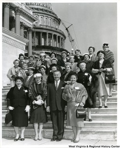 Congressman Arch A. Moore, Jr. standing on the steps of the Capitol with the Republican Women's Federation. The Capitol dome is under construction in the background.