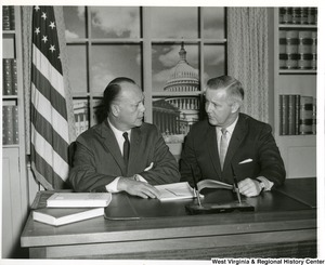 Congressman Arch A. Moore, Jr. talking to Frank A. Seaton, the 36th United States Secretary of the Interior. They appear to be discussing a document on the desk in front of them.