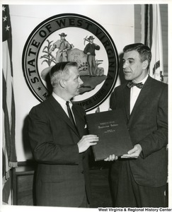 Congressman Arch A. Moore, Jr. being presented a permanently bound volume of the Weirton Steel Employees Bulletin for the year 1960 by Paul Harris, Director of Publications and Publicity of Weirton Steel.  Congressman Moore has arranged for this volume to be permanently preserved in the Library of Congress.