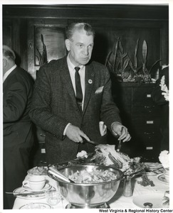 An unidentified man is cutting pieces off a turkey.