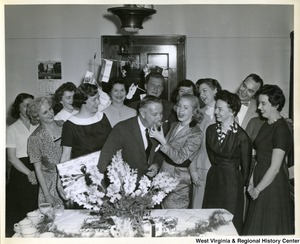 Congressman Arch A. Moore, Jr. (center) celebrating his birthday with staffers. Moore is taking a bite out of a piece of cake.