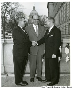 Congressman Arch A. Moore, Jr. shaking hands with an unidentified man. Another unidentified man is standing between them.