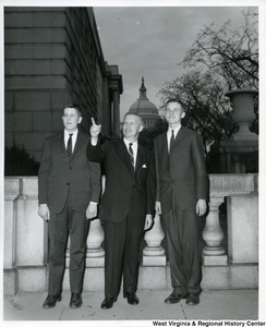 Congressman Arch A. Moore, Jr. (center) pointing out something to two unidentified young men. The Capitol Building can be seen in the background.