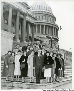 Congressman Arch A. Moore, Jr. (center, front) with an unidentified group of men and women on the steps of the Capitol Building. In the background, the Capitol is under construction.