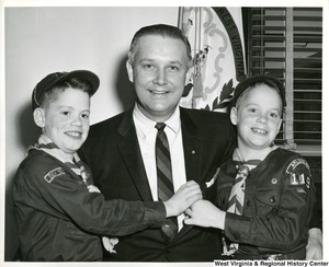 Congressman Arch A. Moore, Jr. with his arms around Boy Scouts Jerry and Gary Southard of Troop 119.