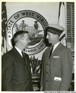"Congressman Arch A. Moore, Jr. talking to an unidentified veteran. The veteran is wearing a hat stating ""Department of West Virginia, Commander of the year 195?"" The seal of West Virginia can be seen in the background."