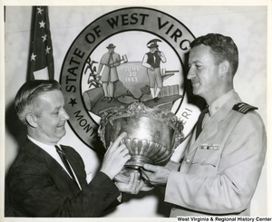 "Congressman Arch A. Moore, Jr. and an unidentified military officer holding a silver bowl, which was given by the citizens of Wheeling to the officer's mess on the U.S. gunboat ""Wheeling"" in September 1897."