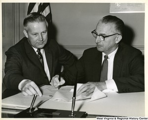 Congressman Arch A. Moore, Jr. (left) watching Congressman McCulloch sign a document.