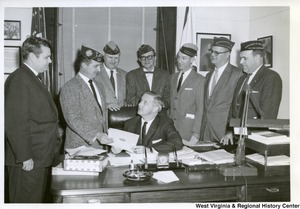 Congressman Arch A. Moore, Jr. (seated) being handed a document from a member of the Veterans of Foreign Wars.  Six other unidentified members are standing around the desk watching.