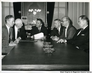 Four unidentified men and Congressman Arch A. Moore, Jr. sitting at a table discussing a document.