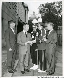 The Weirton High School Band inviting Congressman Arch A. Moore, Jr to accompany them to the Rose Bowl.  Extending the invitation to Moore on the steps of the House of Representatives are Director Charles McKinny, Commander Don Strope, Lt. Matthew Buzzetta, and  Assistant Director Dale Lutton.