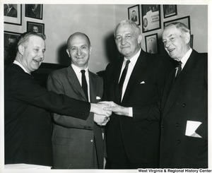 Congressman Arch A. Moore, Jr. clasping hands with three unidentified men.