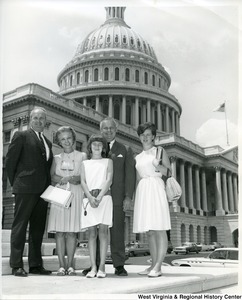 Congressman Arch A. Moore, Jr. standing in front of the Capitol Building with an unidentified family.
