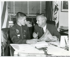 "Congressman Arch A. Moore, Jr. in his office with Boy Scout Robert L. Gore. Robert is one of twelve Boy Scouts chosen from the U.S. to present a ""Report to the Nation"" at a scouting dinner, June 14, in Washington, D.C. Several hundred Scouters, officials of the Government and leaders of national organizations were present. Congressman Moore and Mrs. Moore attended the dinner."