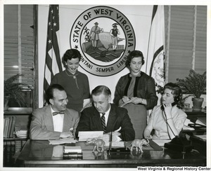 Congressman Arch A. Moore, Jr. (center) with four unidentified individuals, probably staffers. He is sitting at a desk, and one woman is one the telephone.