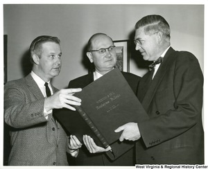 Congressman Arch A. Moore, Jr. (left) with two unidentified men looking at the Weirton Steel Employee Bulletin Volume 28, January thru December 1963.