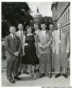Congressman Arch A. Moore, Jr. (left) with five unidentified men and one woman. The Capitol Building can be seen in the background.