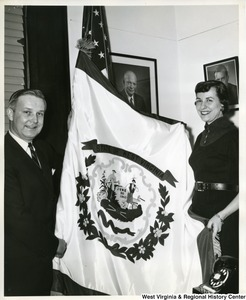 Congressman Arch A. Moore, Jr. and his secretary, Alice Jane Dunn, are unfurling the West Virginia flag in the Congressman's Washington office.