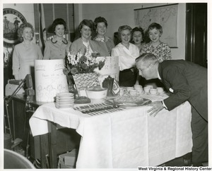 Congressman Arch A. Moore, Jr. blowing out the candles on his  birthday cake while a group of women staffers watch.