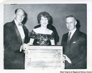 Congressman Arch A. Moore, Jr (right) with an unidentified man and woman. They are standing behind what appears to be a box.