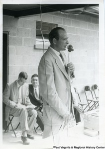 An unidentified man speaking into a microphone during the Ida May dedication. Two men are sitting in chairs behind him.